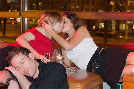 two women kissing, boy asleep in foreground Stock Photo - Premium Royalty-Free, Code: 614-08866197