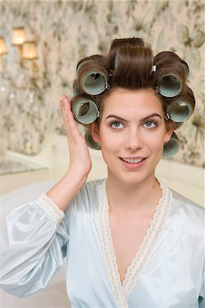 young woman checking her curlers Stock Photo - Premium Royalty-Free, Code: 614-08866576