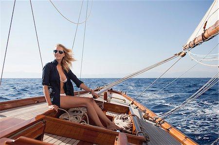woman smiling steering boat Stock Photo - Premium Royalty-Free, Code: 614-08866807