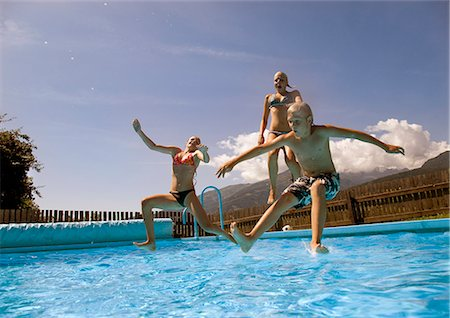 girls and boy jumping into pool Stock Photo - Premium Royalty-Free, Code: 614-08867098