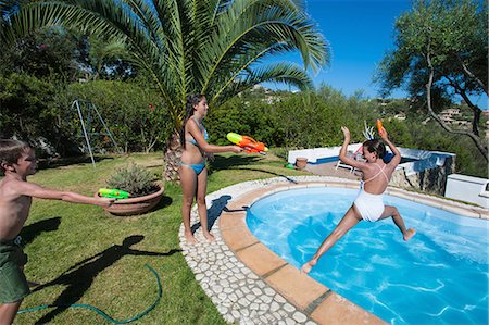 preteen boy shirtless - Children playing in swimming pool Stock Photo - Premium Royalty-Free, Code: 614-08869546