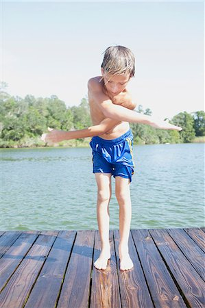 preteen boy shirtless - Boy swinging arms by jetty Stock Photo - Premium Royalty-Free, Code: 614-08874315