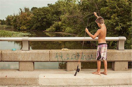 preteen boy shirtless - Boy on bridge with fishing rod Stock Photo - Premium Royalty-Free, Code: 614-08874346