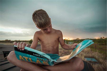 preteen boy shirtless - Boy looking at atlas Stock Photo - Premium Royalty-Free, Code: 614-08874341