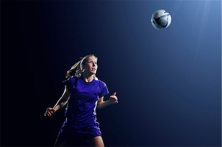 Young female soccer player heading ball Stock Photo - Premium Royalty-Free, Code: 614-08875690