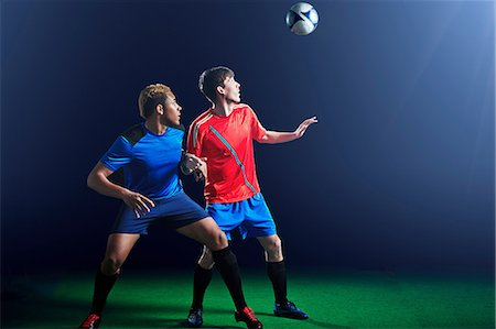 Male soccer players with ball mid air Stock Photo - Premium Royalty-Free, Code: 614-08875700