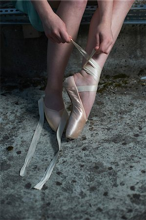 Ballet dancer tying ribbon on ballet shoe Stock Photo - Premium Royalty-Free, Code: 614-08875941