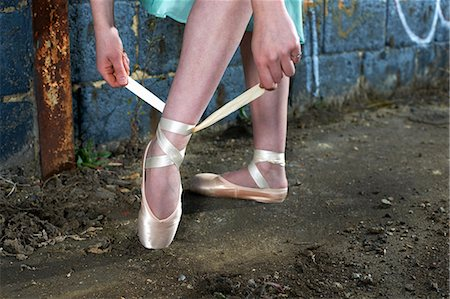 Ballet dancer tying ribbon on ballet shoe Stock Photo - Premium Royalty-Free, Code: 614-08875943