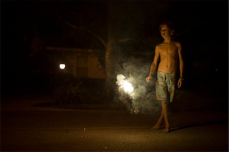 Portrait of boy at night with fireworks in background Destin, Florida, USA Stock Photo - Premium Royalty-Free, Code: 614-08876316