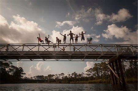 preteen boy shirtless - Man and children leaping from footbridge, Miramar Beach, Florida, USA Stock Photo - Premium Royalty-Free, Code: 614-08876324