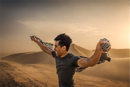 extreme terrain - Man holding scarf in wind, Glamis sand dunes, California, USA Stock Photo - Premium Royalty-Free, Code: 614-08876674