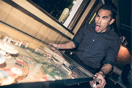 pinball - Young man playing pinball in bar, excited expression Stock Photo - Premium Royalty-Free, Code: 614-08877616