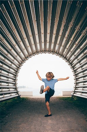 Boy in corrugated tunnel, arm open leg raised Stock Photo - Premium Royalty-Free, Code: 614-08879330