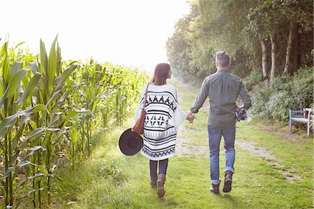 Rear view of couple strolling and holding hands in field Stock Photo - Premium Royalty-Free, Code: 614-08879473