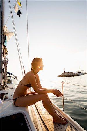 Woman in bikini sitting on boat Stock Photo - Premium Royalty-Free, Code: 614-08870978