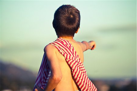 preteen boy shirtless - Boy pointing into distance with striped fabric on shoulder Stock Photo - Premium Royalty-Free, Code: 614-08873700