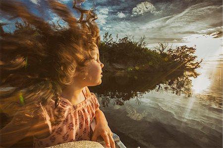 Young girl enjoying cruise on river, eyes closed basking in sunlight, Homosassa, Florida, USA Stock Photo - Premium Royalty-Free, Code: 614-08884778