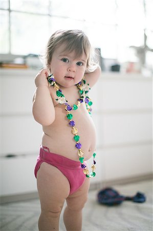 Portrait of female toddler trying on bead necklace in kitchen Stock Photo - Premium Royalty-Free, Code: 614-08908441