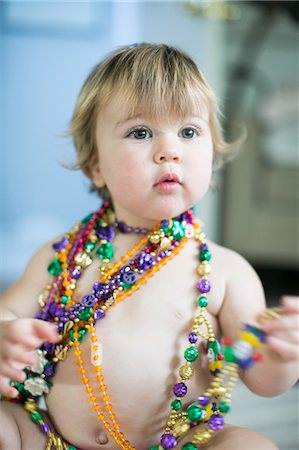 Female toddler trying on bead necklaces in kitchen Stock Photo - Premium Royalty-Free, Code: 614-08908442