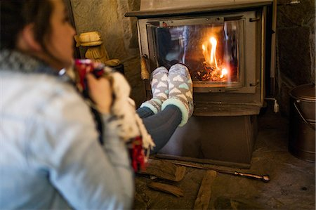 female 16 year old feet - Young woman warming feet in front of fire Stock Photo - Premium Royalty-Free, Code: 614-08908558