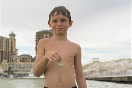 Boy holding blue crab, Gulf of Mexico, Emerald Coast, Florida, USA Stock Photo - Premium Royalty-Free, Code: 614-08926353
