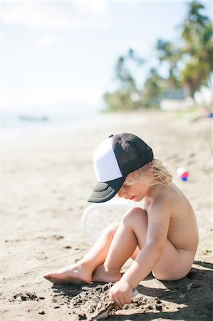 Young boy sitting on beach, digging in sand Stock Photo - Premium Royalty-Free, Code: 614-08926591
