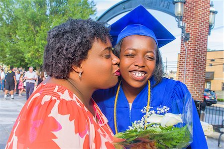 Mother kissing daughter on her graduation day Stock Photo - Premium Royalty-Free, Code: 614-08990482