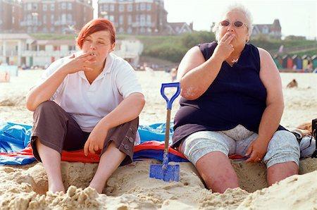 Two women smoking on the beach Stock Photo - Premium Royalty-Free, Code: 614-00379590