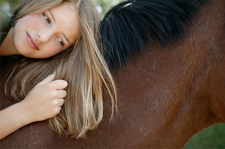 Young woman lying on her horse Stock Photo - Premium Royalty-Free, Code: 614-00602852