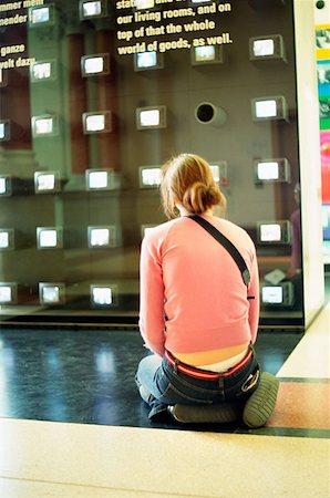 Girl kneeling in art gallery Stock Photo - Premium Royalty-Free, Code: 614-00657339