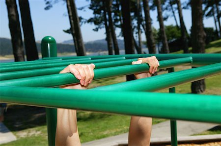 Person hanging onto monkey bars Stock Photo - Premium Royalty-Free, Code: 614-00683923