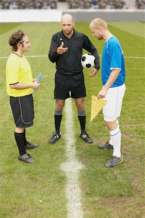 Referee tossing a coin Stock Photo - Premium Royalty-Free, Code: 614-00808626