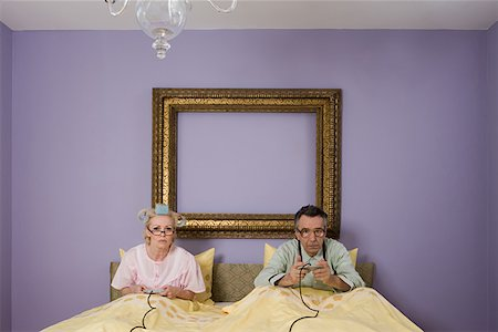 Senior couple playing video game in bed Stock Photo - Premium Royalty-Free, Code: 614-01028110