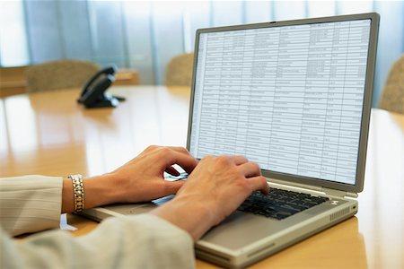 Businesswoman using laptop Stock Photo - Premium Royalty-Free, Code: 614-01071420