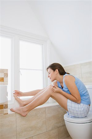 Woman painting toenails Stock Photo - Premium Royalty-Free, Code: 614-01179719