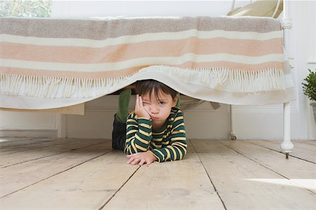 Boy hiding under a bed Stock Photo - Premium Royalty-Free, Code: 614-01821729