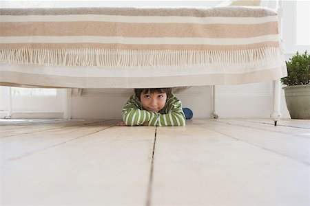 Boy hiding under a bed Stock Photo - Premium Royalty-Free, Code: 614-01821745