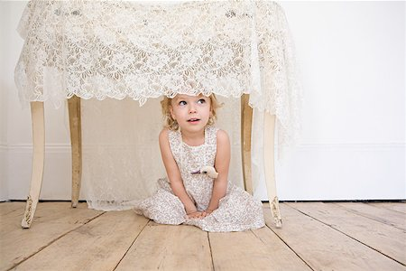 Girl hiding under a table Stock Photo - Premium Royalty-Free, Code: 614-01821751