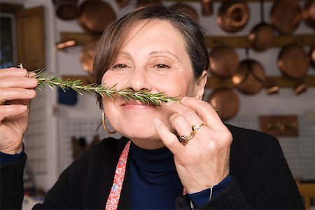 Woman smelling a sprig of rosemary Stock Photo - Premium Royalty-Free, Code: 614-02049362