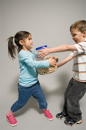 student fighting - A boy and girl fighting over a jar of biscuits Stock Photo - Premium Royalty-Free, Code: 614-02051069