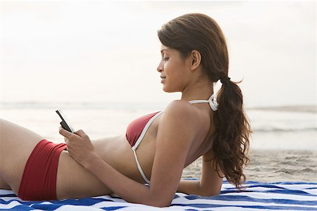 Woman on beach with cellphone Stock Photo - Premium Royalty-Free, Code: 614-02259810