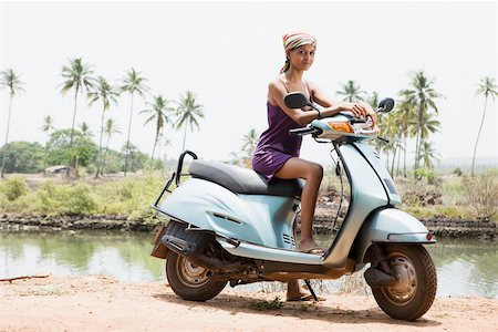 Young woman on moped Stock Photo - Premium Royalty-Free, Code: 614-02259838