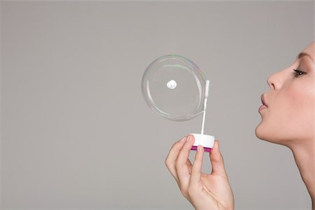 Young woman blowing a bubble Stock Photo - Premium Royalty-Free, Code: 614-02393730