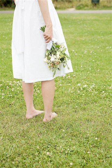 Bride standing on grass Stock Photo - Premium Royalty-Free, Image code: 614-02612526