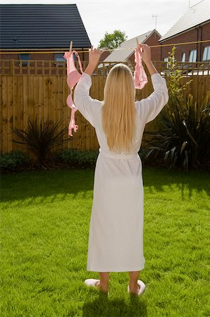 Woman putting lingerie in washing line Stock Photo - Premium Royalty-Free, Code: 614-02613121