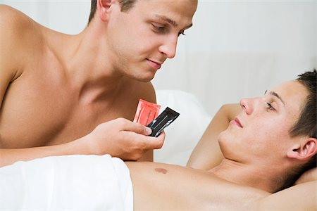 A man handing condoms to his partner Stock Photo - Premium Royalty-Free, Code: 614-02613474