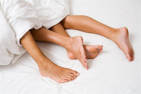 Legs sticking out of a duvet Stock Photo - Premium Royalty-Free, Code: 614-02613486