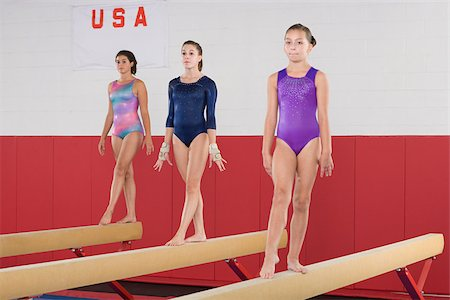 preteen girls gymnastics - Gymnasts on a balance beam Stock Photo - Premium Royalty-Free, Code: 614-02640257