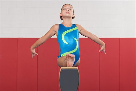 preteen girls gymnastics - Gymnast doing the splits on a balance beam Stock Photo - Premium Royalty-Free, Code: 614-02640253