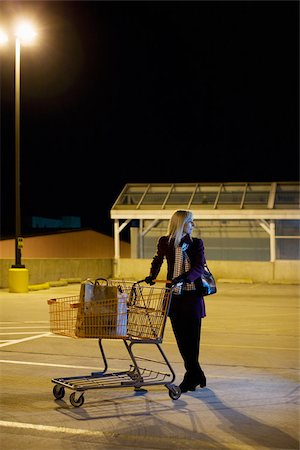 empty shopping cart - Woman alone in supermarket parking lot Stock Photo - Premium Royalty-Free, Code: 614-02739729